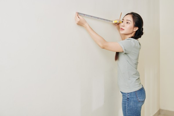 woman holding measuring tool up to wall